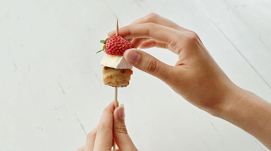 Würfel Putenbrust als Basis aufspießen, dann einen Würfel Géramont Mini, zum Schluss eine halbeErdbeere.