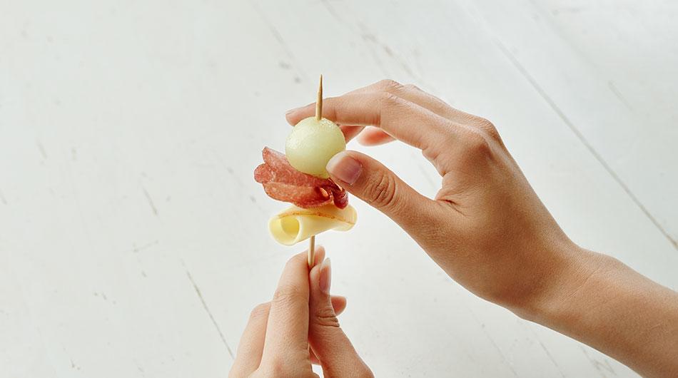 Scheibe Géramont fein-würzigaufspießen, dann eine Scheibe Baguettesalami und zum Schlusseine fruchtige Kugel Honigmelone.