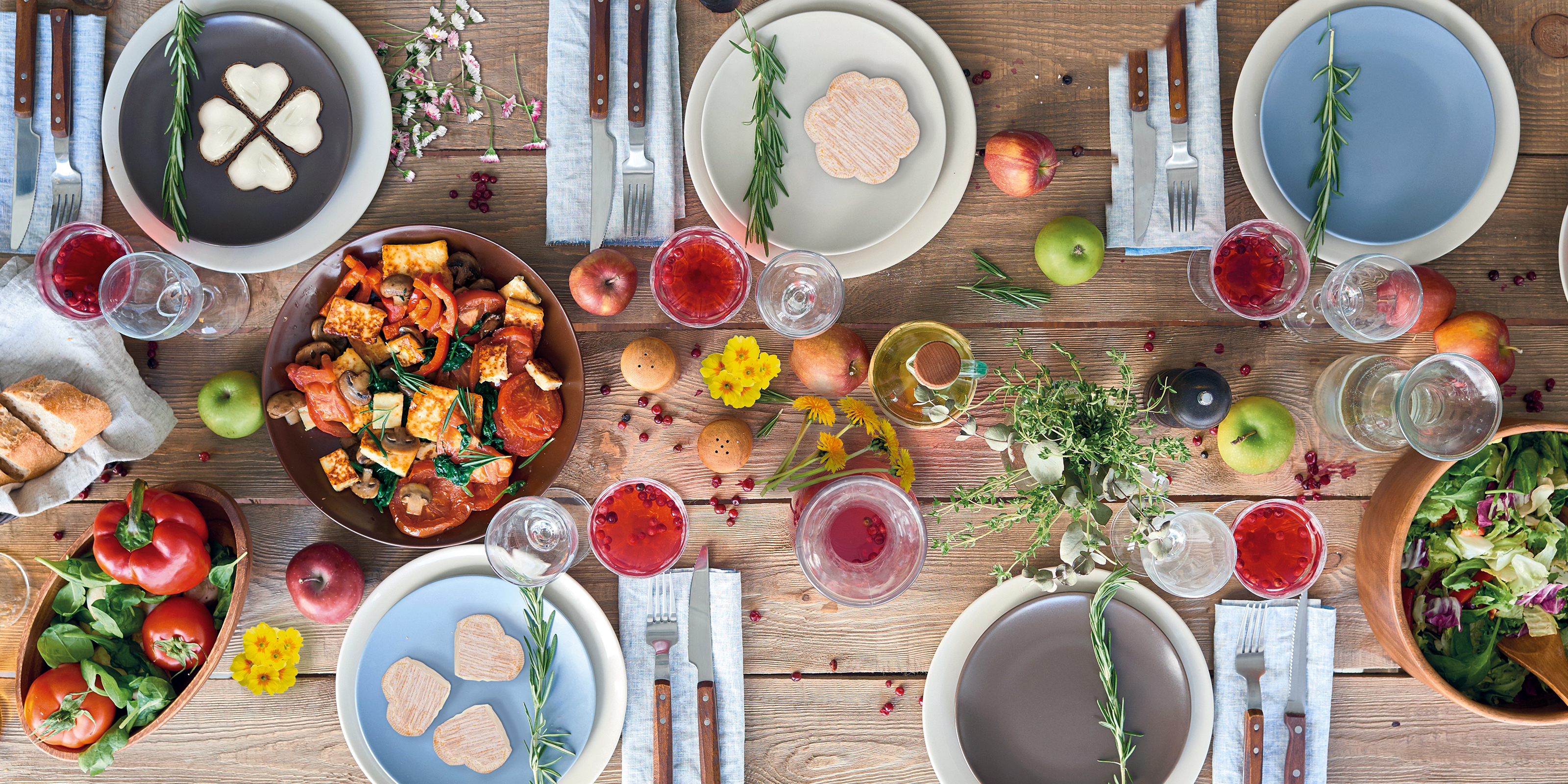 Bunt dekorierter Tisch zum Frühlingsanfang mit Blumen, Obst und Gemüse